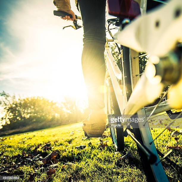 Young woman cycling in the park at sunse