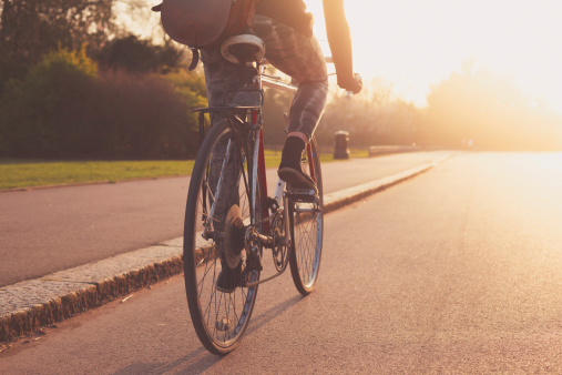 Young woman cycling in the park at sunset 493958393