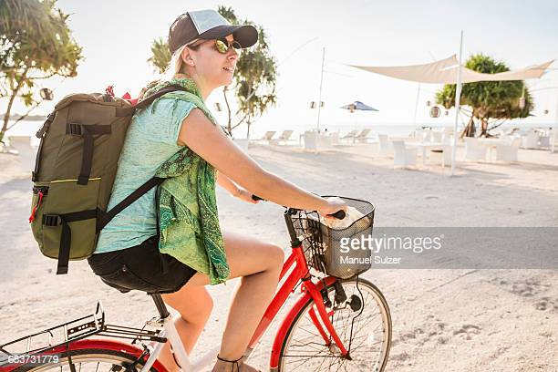 Young woman cycling on beach, Gili Meno, Lombok, Indonesia