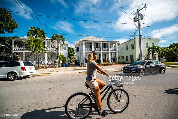 Young woman cycling on Key West street, Florida, USA