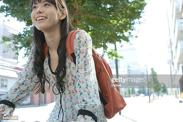 Young woman cycling on street, smiling