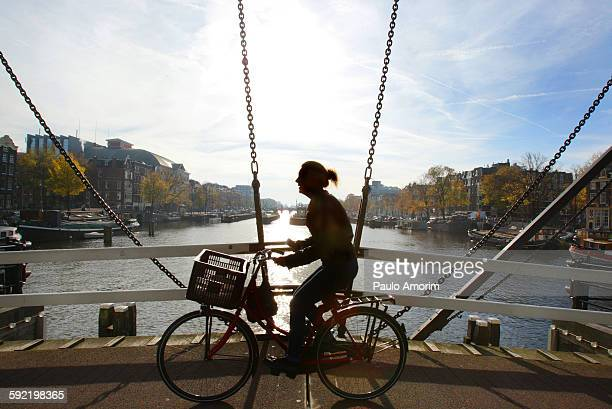 A young woman cycling on the bridge in Amsterdam