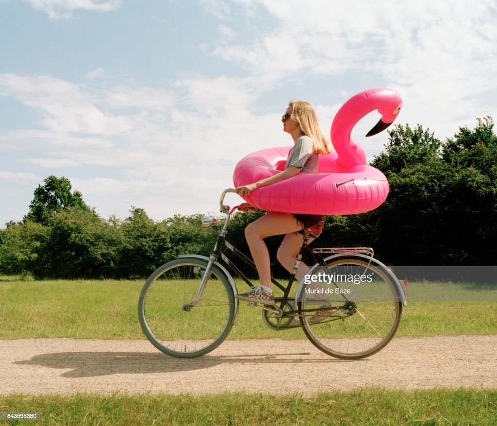 Young woman cycling with flamingo ring : Stock Photo