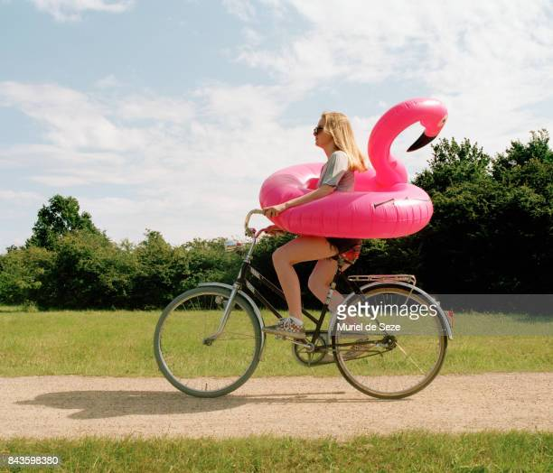 Young woman cycling with flamingo ring