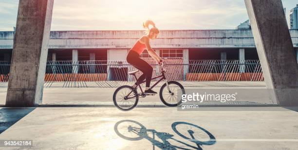 young woman cycling with flatland bmx - bmx cycling stock pictures, royalty-free photos & images