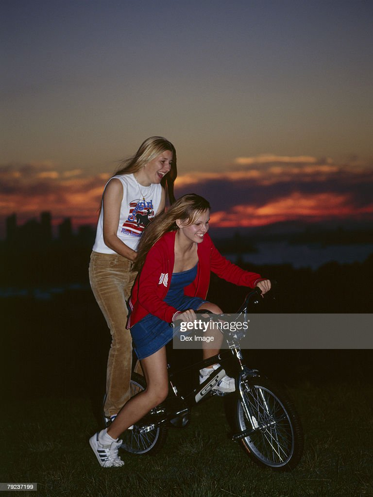 Young woman cycling with young woman on back of bike : Stock Photo