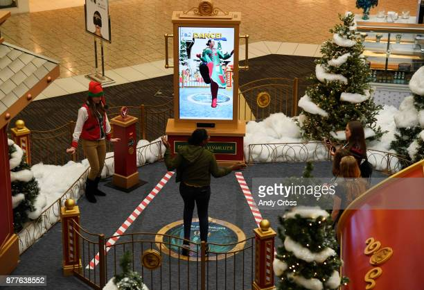 A young woman dances at Santa's Flight Suit Visualizer at Santa's Flight Academy at the Cherry Creek Mall November 22 2017 Young visitors of the...