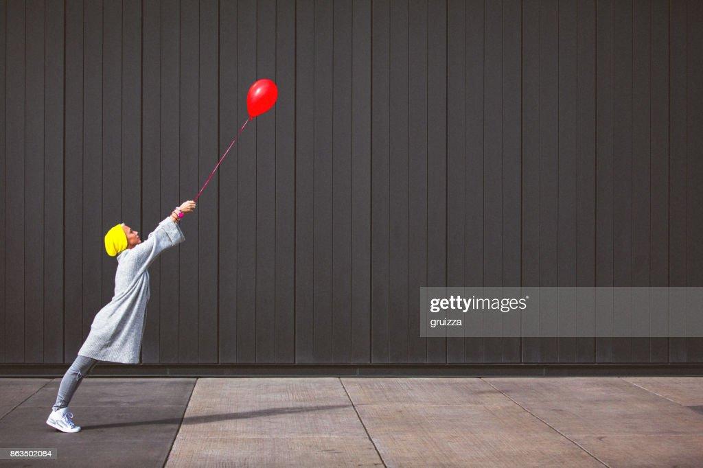 Jeune femme danse et maintenant le ballon rouge contre le mur gris : Photo