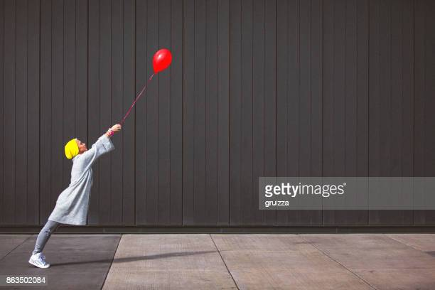 young woman dancing and holding red balloon against the grey wall - contrasti foto e immagini stock