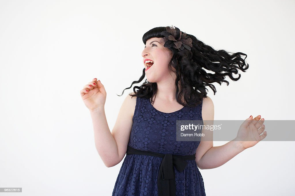 Young woman dancing and shaking her hair, laughing : Stock Photo