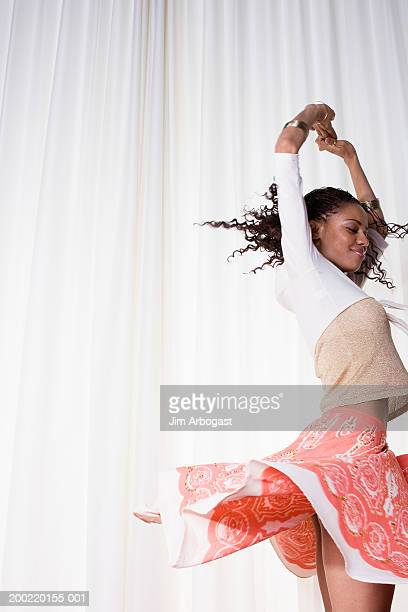 young woman dancing, arms raised, side view - black skirt stock pictures, royalty-free photos & images