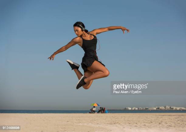 Young Woman Dancing At Beach Against Clear Sky