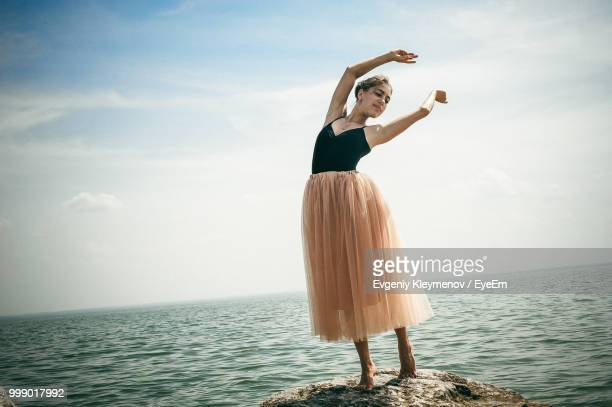 Young Woman Dancing At Beach Against Sky