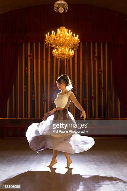 young woman dancing barefoot in ballroom - balzaal stockfoto's en -beelden