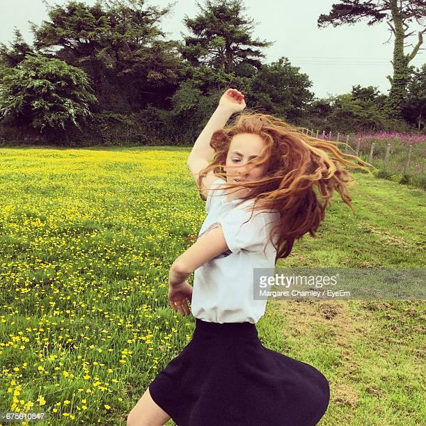 Young Woman Dancing By Buttercup Flowers Growing On Field