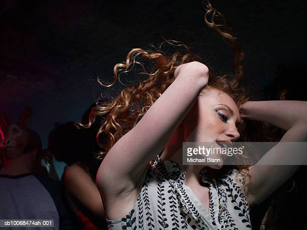 young woman dancing in night club - incidental people stock pictures, royalty-free photos & images