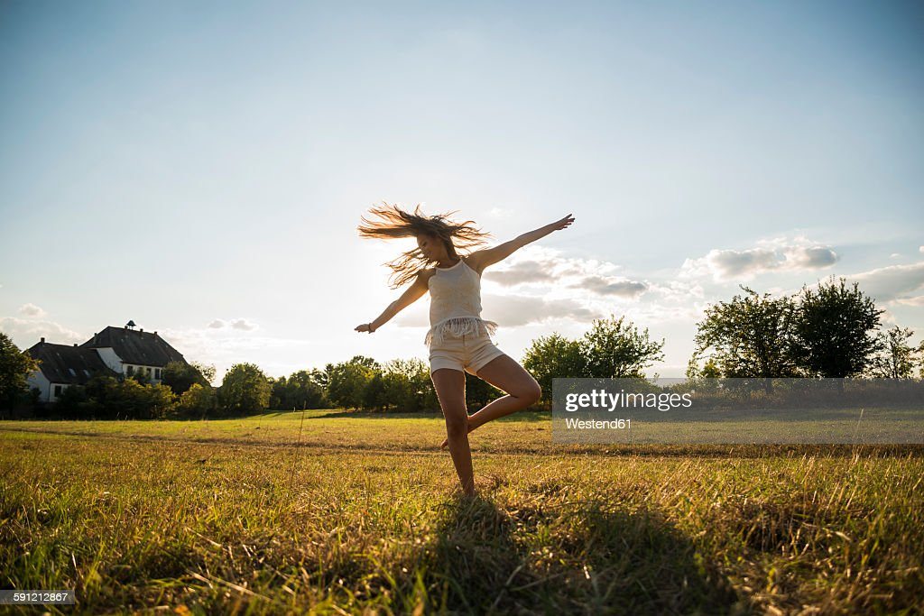 Young woman dancing on a meadow at backlight : Stock-Foto