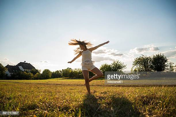 Young woman dancing on a meadow at backlight