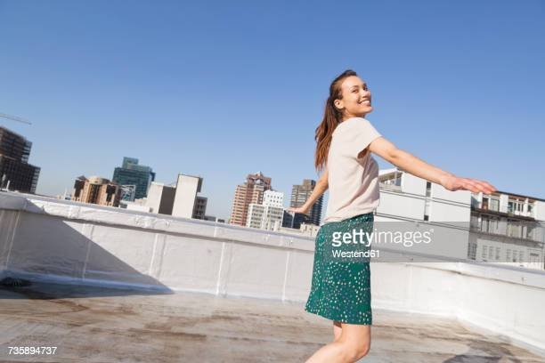 Young woman dancing on a rooftop terrace