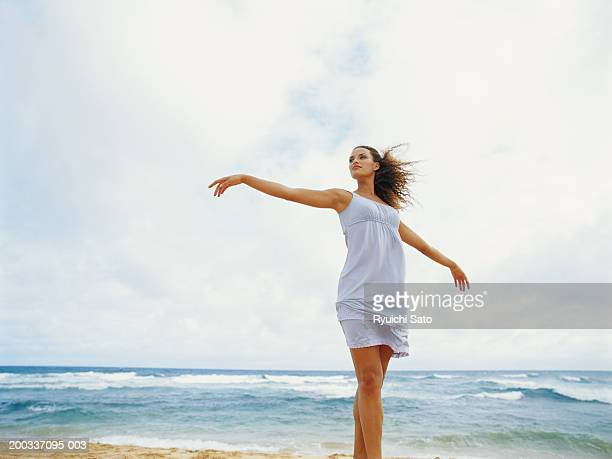 Young woman dancing on beach, low angle view