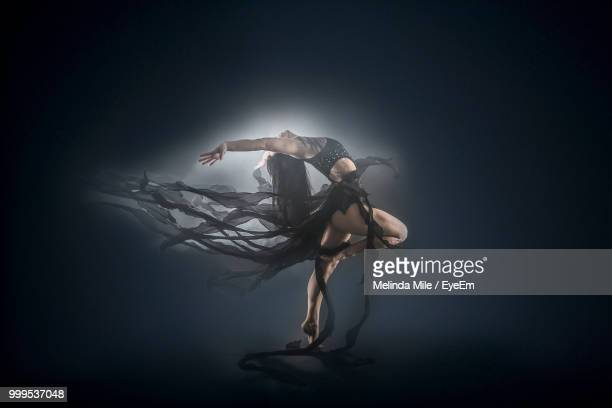 Young Woman Dancing On Box Against Black Background