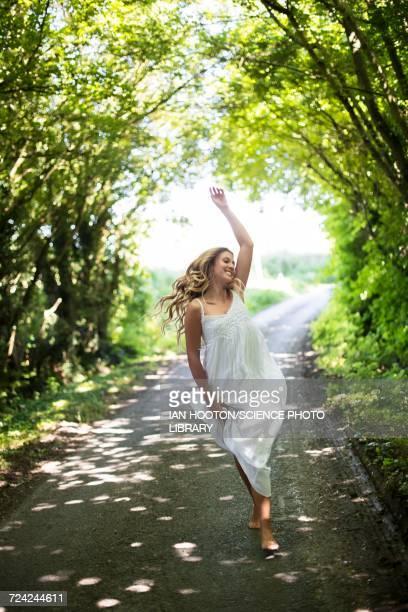 young woman dancing on country lane - weißes kleid stock-fotos und bilder