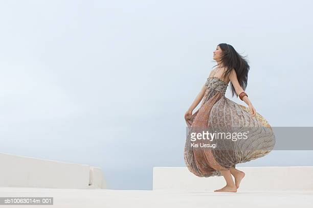 Young woman dancing on roof, smiling