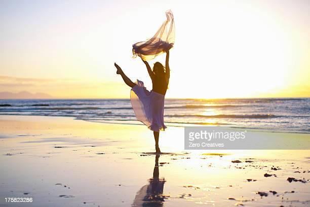 young woman dancing on sunlit beach - tänzerin stock-fotos und bilder