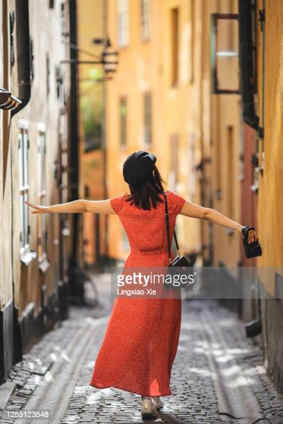 young woman dancing on the cobbled narrow alley in gamla stan, the old town in central stockholm, sweden - stockholm stock pictures, royalty-free photos & images