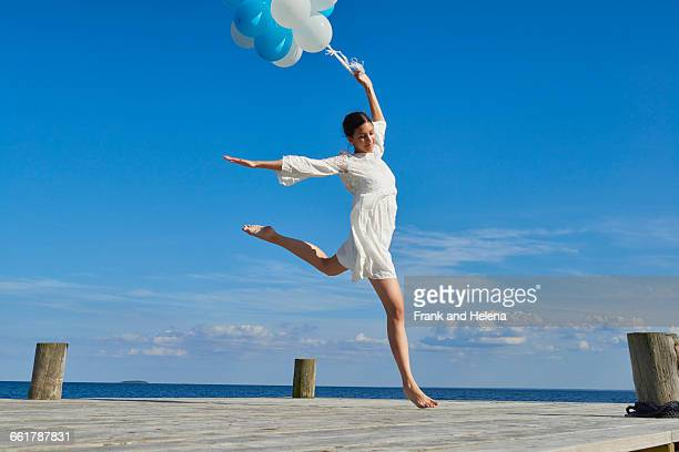 young woman dancing on wooden pier, holding bunch of balloons - ダンス ドレス ストックフォトと画像