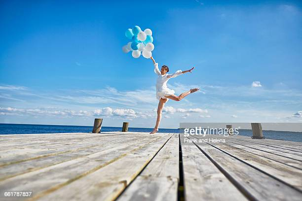 Young woman dancing on wooden pier, holding bunch of balloons