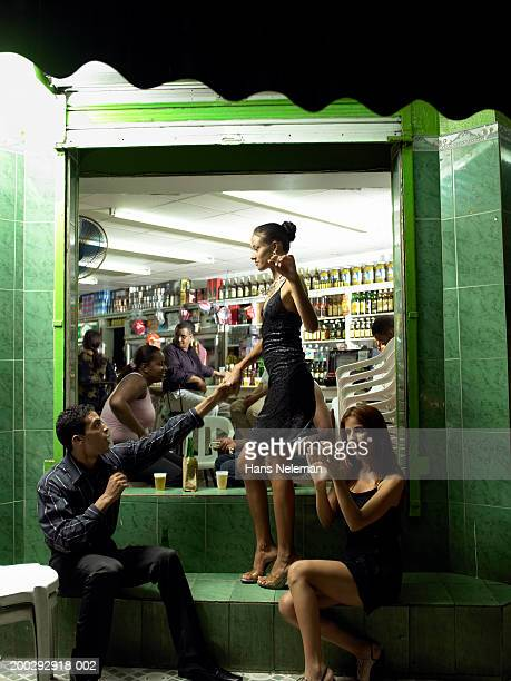 Young woman dancing outside bar with friends, side view