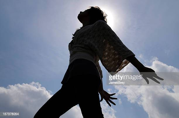 Young Woman Dancing Silhouetted by Sun, Blue Sky Clouds Background