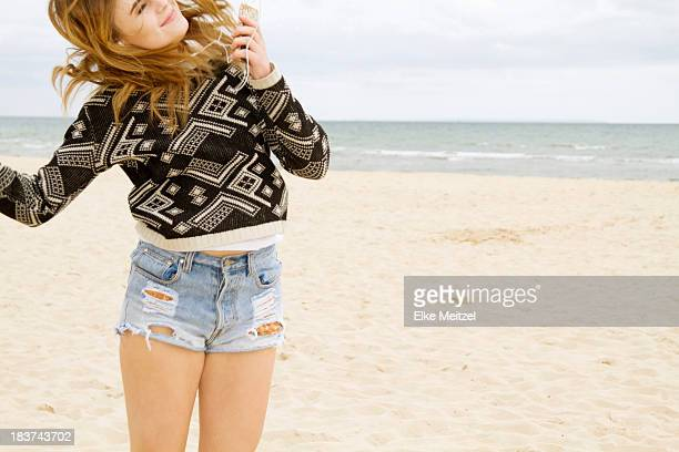 Young woman dancing to MP3 player on beach