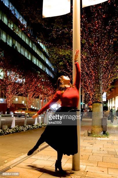 クリスマス イルミネーションの下で踊っている若い女性