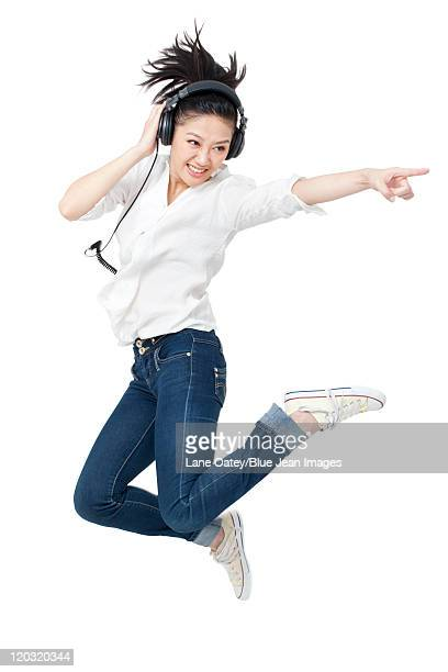 Young woman dancing while listening to headphones