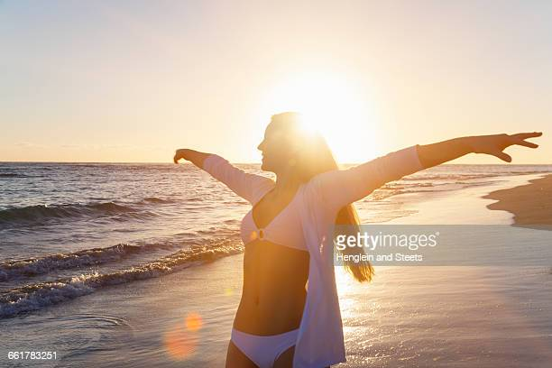 Young woman dancing with arms open on beach at sunset, Dominican Republic, The Caribbean