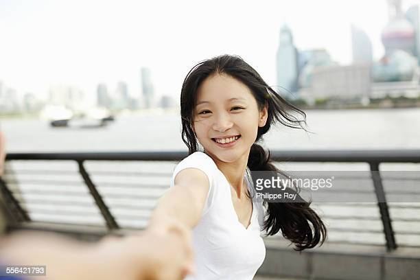 Young woman dancing with boyfriend on the waterfront, The Bund, Shanghai, China