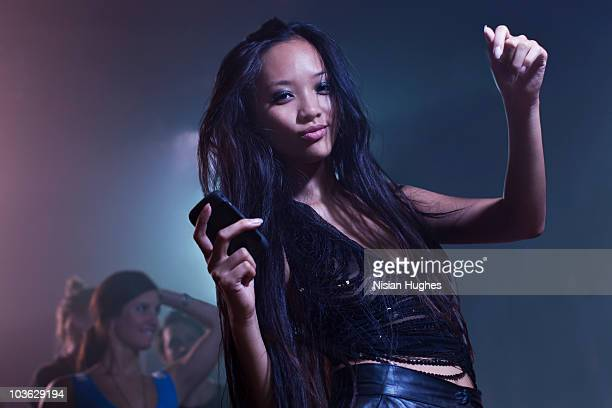 Young woman dancing with cell phone