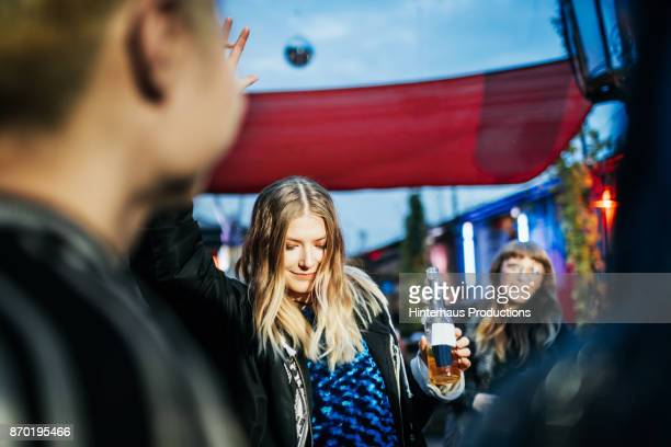 Young Woman Dancing With Drink At Open Air Nightclub