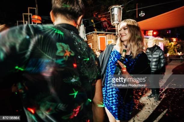 Young Woman Dancing With Friends At Colourful Open air Nightclub