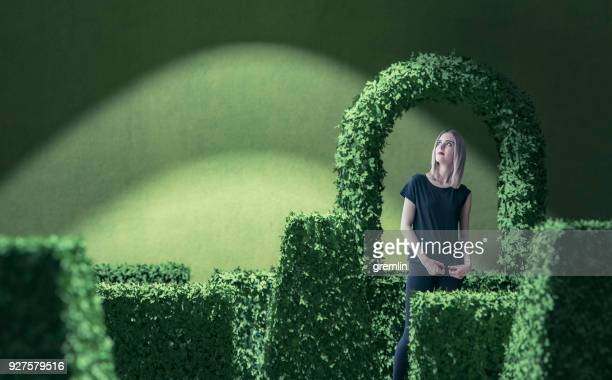 young woman day dreaming about green park - topiary stock photos and pictures