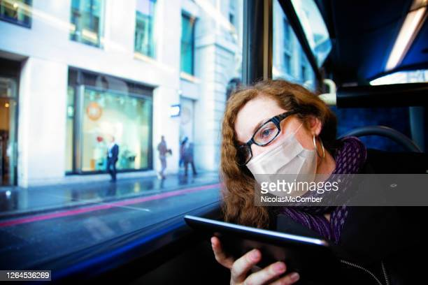 young woman day dreaming in bus while holding a tablet and wearing a protective mask - long hair stock pictures, royalty-free photos & images