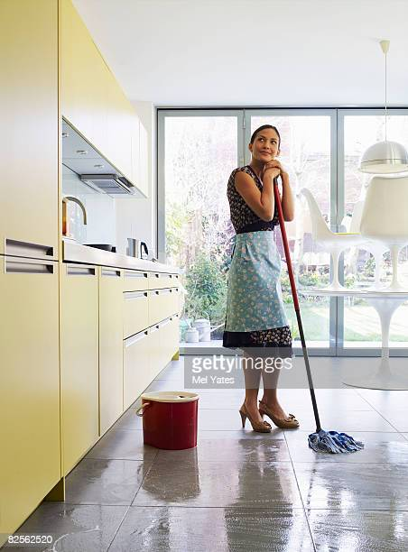 Young woman daydreaming, holding mop