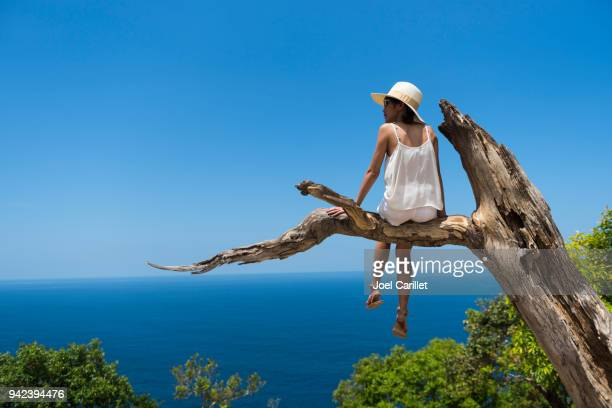 Young woman daydreaming in a tree (Nusa Penida, Indonesia)