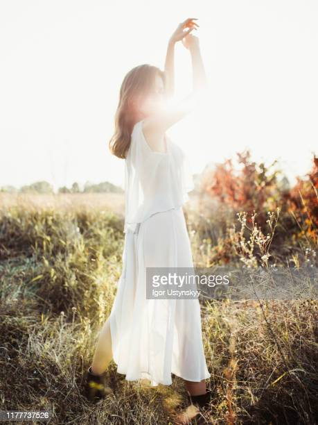 young woman daydreaming in field - women wearing see through clothing stock pictures, royalty-free photos & images