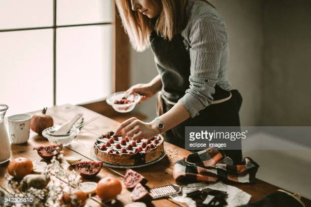 young woman decorating cake - christmas cake stock photos and pictures