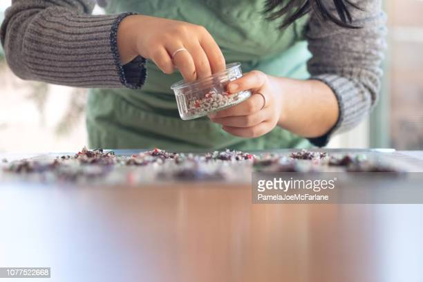 young woman decorating christmas chocolates with crushed candy cane sprinkles - hygge stock pictures, royalty-free photos & images