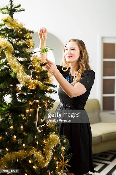 young woman decorating christmas tree - decoration stock pictures, royalty-free photos & images