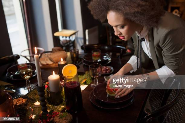 Young woman decorating plate with food at table during Christmas